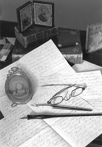 Black and white photo of old-fashioned letters and pens on desk